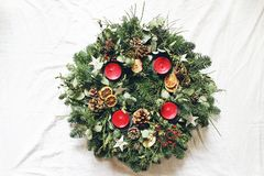 Christmas advent wreath isolated on white table background. Decorated by evergreen fir tree branches, eucalyptus leaves. Wooden stars, pine cones, berries and royalty free stock photo