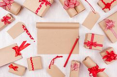 Christmas advertising background with blank craft notepad, gifts with red pencil, bows and ribbon on white wood board, top view. Christmas advertising royalty free stock images