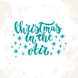 Christmas in the Air - lettering Christmas and New Year holiday calligraphy phrase  on the sketch background Royalty Free Stock Photo