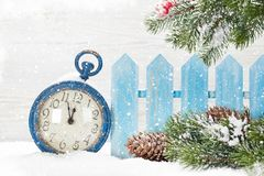Christmas alarm clock and fir tree. Branch covered by snow in front of wooden wall Royalty Free Stock Image