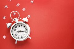 Christmas alarm clock with snowflakes and copy space on red  bac. Kground.  Christmas timer. Time to celebrate Stock Photography