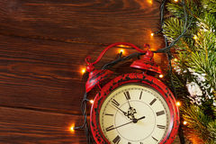 Christmas alarm clock, tree branch and lights Royalty Free Stock Photo