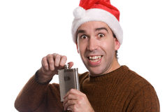 Christmas Alcohol. A young man smiling and holding a flask of alcohol, isolated against a white background Stock Photos