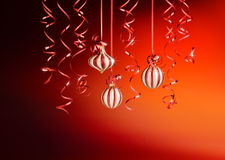 Christmas ambience. Christmas decorations with ribbons and balls over red background Royalty Free Stock Image