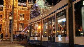Christmas in Amsterdam, Holland. Tram drives past the central railway station decorated with a christmas tree for Christmas in Amsterdam, Holland on December 12 stock video footage