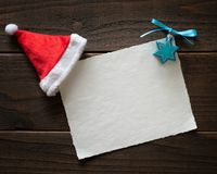 Free Christmas And Hannukah Blank Happy Holidays Card On Rustic Boards With White Paper, A Santa Hat And Hanukah Decoration. Royalty Free Stock Photos - 163015338