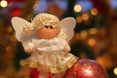 Christmas angel. Smiling girl with glass ball covered with golden stars. Lights of Christmas tree in background royalty free stock photography