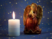 Christmas Angel. A candle with Christmas angel on background with stars royalty free stock photos