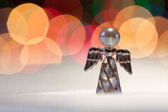 Christmas angel. Angel figurine on snowy underlay and colour lights on background Royalty Free Stock Images