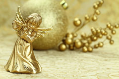 Christmas angel. Playing a flute with golden decoration at the background Royalty Free Stock Photo
