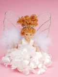 Christmas angel. Shot of a christmas angel decoration against a pale pink background Royalty Free Stock Photography