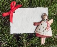 Christmas, angel, blank paper on evergreens Stock Photos