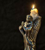 Christmas angel candle. A pewter figuring candleholder of a praying Christmas angel with a burning wax candle Royalty Free Stock Images