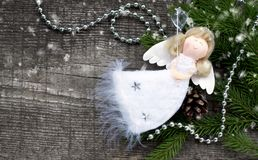 Christmas angel. Christmas white angel with snow and fir tree on wooden background stock photo