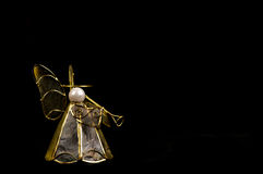 Christmas angel decoration with trumpet on black. Decorative mother of pearl and brass Christmas angel with a trumpet, on black Stock Image
