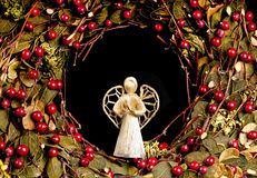 Christmas angel decoration in a wreath. Decorative raffia Christmas angel inside a Christmas wreath with green leaves and red berries.  On black Royalty Free Stock Images
