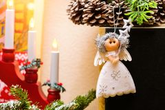 Christmas angel doll hanging on wreath with cones stock image