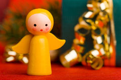 Christmas angel with gift. Small yellow christmas angel with decorated gift Stock Photos