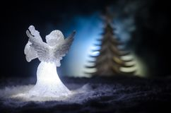 Christmas Angel glass xmas figure and glass fir tree, christmas tree, docorative elements on dark background. Christmas decoration Stock Photo