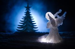 Christmas Angel glass xmas figure and glass fir tree, christmas tree, docorative elements on dark background. Christmas decoration. Angel xmas concept Stock Image