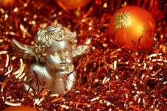 Christmas Angel - Orange. An orange Christmas theme - a little bust of an angel with golden and silver metallic coat in orange decoration - lametta strings, with Stock Image