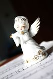 Christmas angel playing carrols. Ceramic white angel playing the flute on sheet of note paper Royalty Free Stock Photo