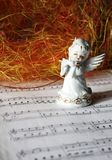 Christmas angel playing the flute. Ceramic white angel playing the flute on sheet of note paper Royalty Free Stock Photos