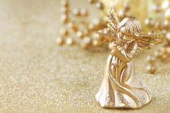 Christmas angel. Playing a flute with golden decoration at the background stock image