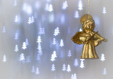 Christmas angel playing the violin. Christmas decoration, Christmas card, for writing holiday greetings. Background with blue Christmas trees Stock Photography