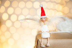Christmas angel in a red hat. Sitting on a gift box Royalty Free Stock Photo