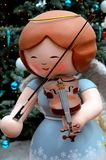 Christmas angel statue with wings in blue dress plays violin with bow. Singapore - December 7, 2016: A female angel with wings statue with a gold halo wears a Stock Images