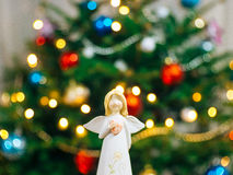 Christmas angel on a wooden table. On a background of trees royalty free stock image