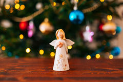 Christmas angel on a wooden table. On a background of trees stock photography