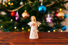 Christmas angel on a wooden table. On a background of trees stock image
