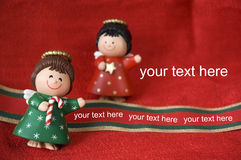 Christmas angels. Two Christmas angels present your text on red background Royalty Free Stock Photos