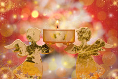 Christmas angels candle. Over bright red background royalty free stock photo