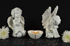 Christmas angels with flowers for gifts, isolated on black Stock Image