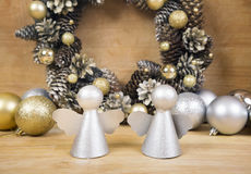 Christmas angels with wreath of cones on background. Stock Photo