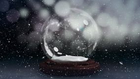 Christmas animation of snow globe against bokeh background