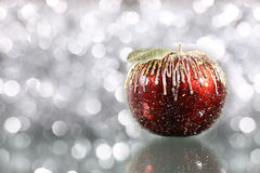 Christmas apple. On silver blurred background stock image