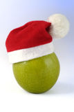 Christmas Apple. Green apple with a christmas hat Royalty Free Stock Photography