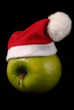 Christmas Apple. Green apple with a christmas hat Stock Images