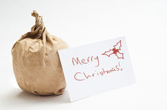 Christmas Apple in Brown Paper. Conceptual image to convey a frugal Christmas. An apple wrapped in brown paper with a gift card royalty free stock images