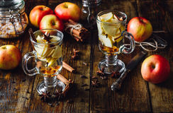 Christmas Apple Drink. Glasses of Christmas Apple Drink with Clove, Cinnamon, Anise Star and Dark Candy Sugar. All Ingredients and Some Kitchen utensils on stock photo