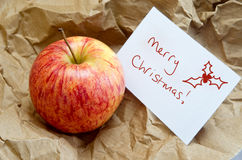 Christmas Apple Gift in Brown Paper. Conceptual image to convey a frugal Christmas. An apple surrounded by brown wrapping paper, with a Christmas gift message stock photography