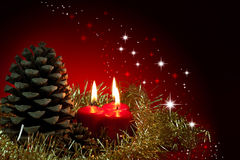 Christmas arangement. Christmas decoration.Three red burning candles and pinecone Stock Image