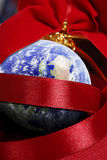 Christmas around the world. A world christmas decoration wiht red ribbon Royalty Free Stock Image