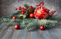 Christmas arrangement with baubles, fir twigs and frosted berrie. S on rustic wooden table Royalty Free Stock Photo
