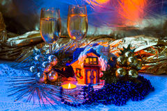 Christmas arrangement with ceramic cabin, candles, wine glasses and Christmas decorations. Stock Images