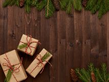 Christmas arrangement of gifts in Kraft paper on brown wooden ba Royalty Free Stock Image
